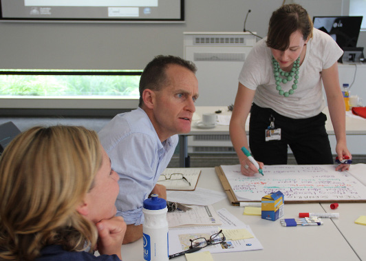 Three of the workshop organisers (from the left) Martine Maron, Andrew Macintosh and Megan Evans, capture some of the groups thinking on butchers' paper.