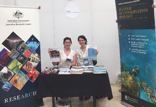Maria Martinez-Harms (left) and Rebecca Runting showcase the English and the Spanish versions of Decision Point on the CEED booth at ICCB 2017.